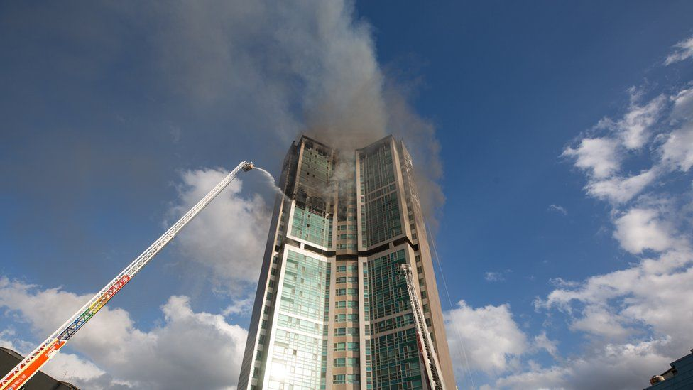 Firefighters extinguish a fire at an apartment building in Ulsan, South Korea, 09 October 2020.