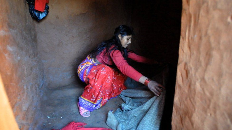 A teenaged girl in Nepal prepares her bedding inside a 'chhaupadi house' in the village of Achham, some 800km west of Kathmandu (23 November 2011)