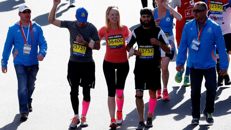 Marathon bombing survivor Adrianne Haslet-Davis crosses the finish line of the 118th Boston Marathon
