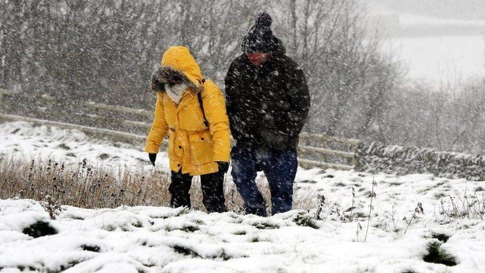 Walkers in the snow near Castleton in the Peak District