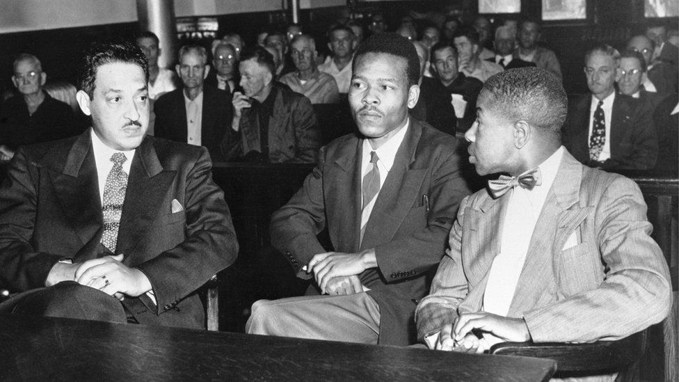 One of the pardoned men, Walter Irvin, speaks with his lawyers during his retrial