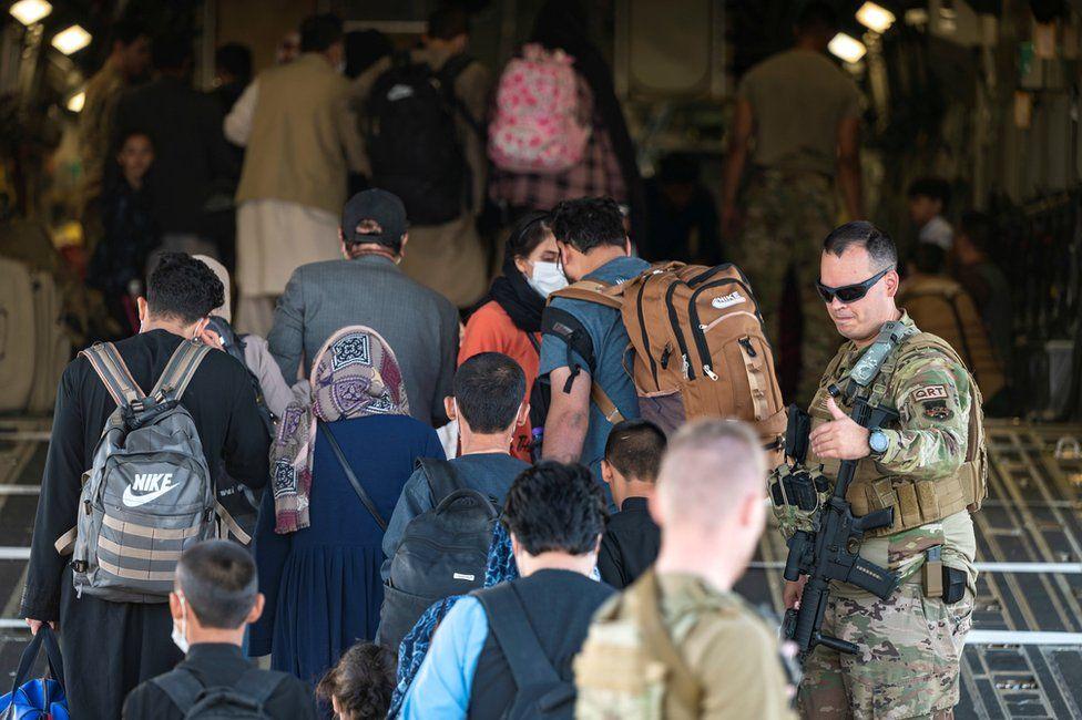 Guía de aviadores de la Fuerza Aérea de los EE. UU. a evacuados calificados a bordo de un C-17 Globemaster III de la Fuerza Aérea de los EE. UU. en el Aeropuerto Internacional Hamid Karzai (HKIA), Afganistán, 24 de agosto de 2021
