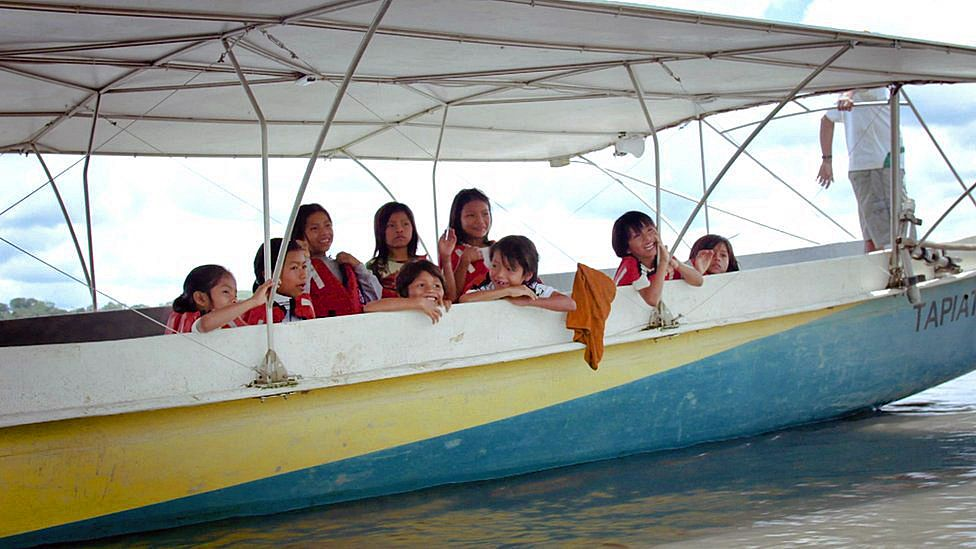 Children on the solar canoe on their way to school