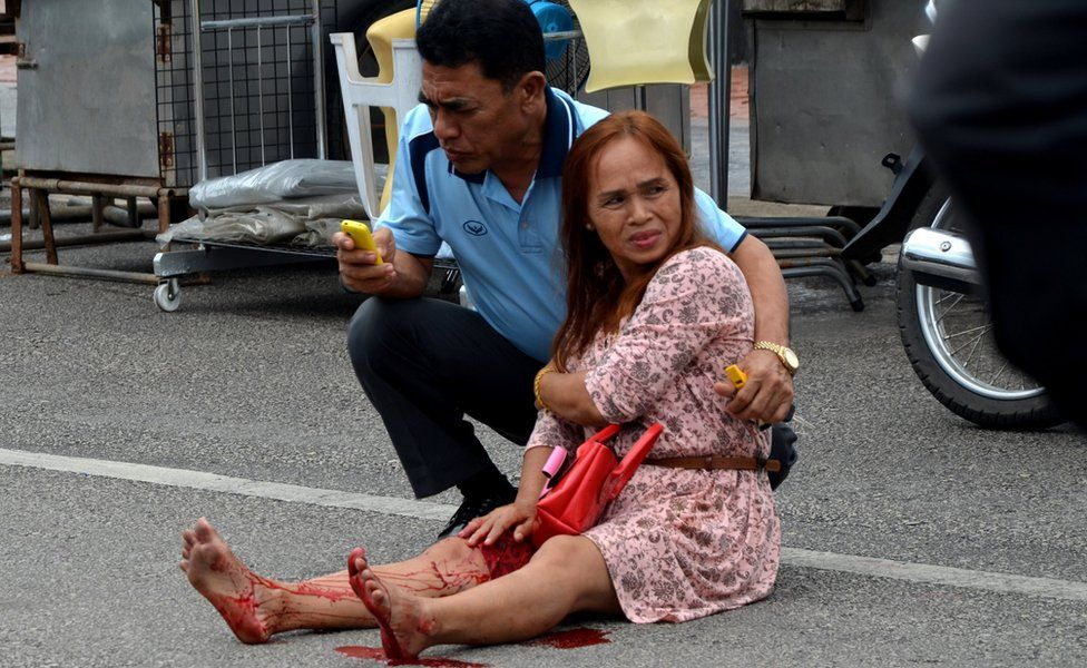 An injured woman sitting in the road after a bomb exploded on 11 August 2016 in Trang.