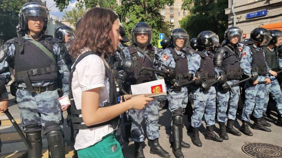 Olga walking in front of police with a copy of the Russian constitution