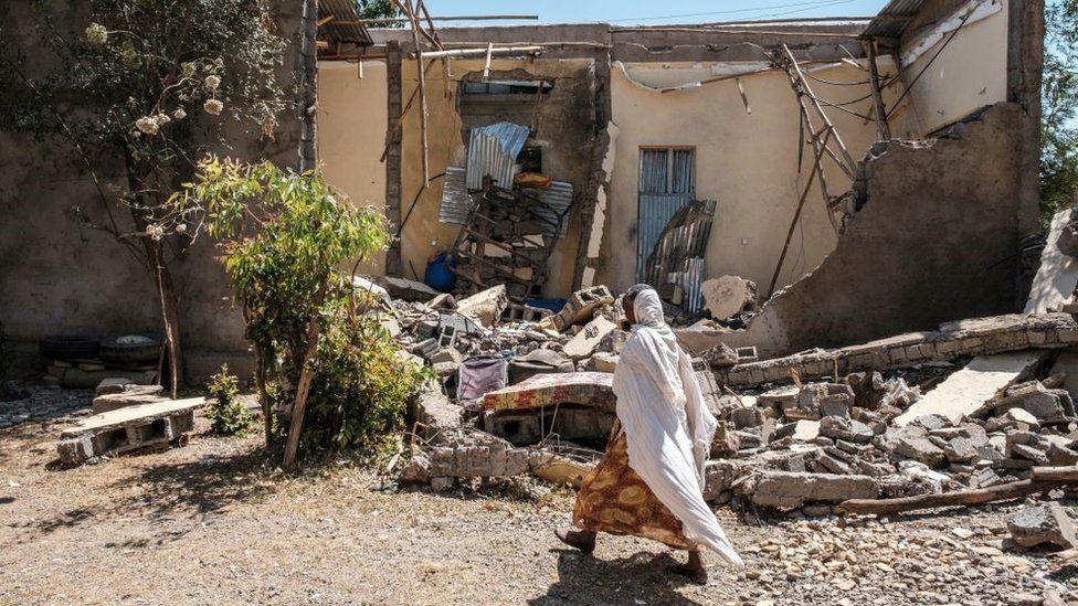 Une femme marche devant une maison endommagée qui a été bombardée lorsque les forces fédérales sont entrées dans la ville, à Wukro, au nord de Mekele, le 1er mars 2021