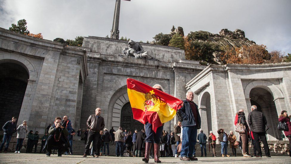A woman waves a Spanish flag outside the Valley of the Fallen memorial near Madrid