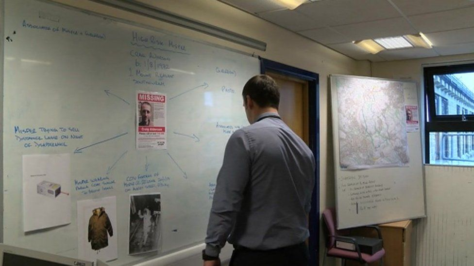 A police officers assessing a missing persons board at Halifax police station