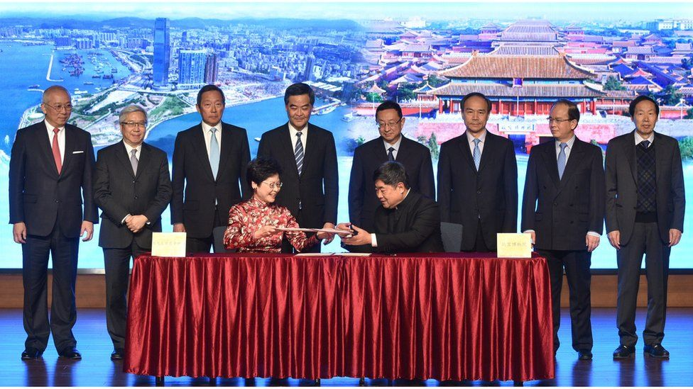 Ms Lam seated at the signing ceremony, with one man seated next to her and eight officials standing behind.