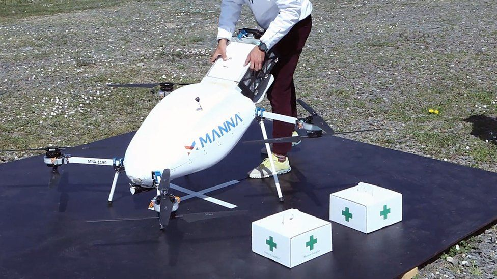 A worker loads a drone with a large rail-guided system