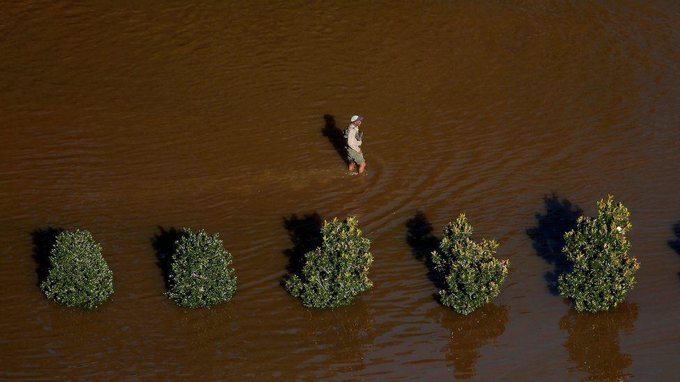 A man walks through flood waters after Hurricane Matthew in Lumberton, North Carolina October 10, 2016.