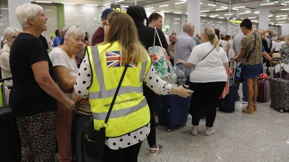 British Government officials help Thomas Cook passengers at Palma the Mallorca airport