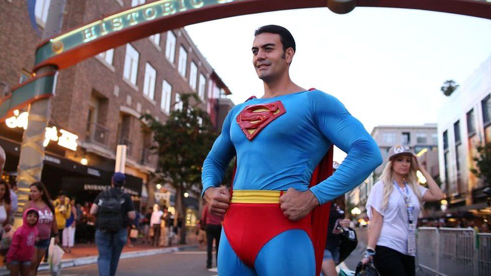 A Cosplay character dressed as Superman, poses for pictures along 5th Avenue in the Gaslamp Quarter during Comic Con International on July 20, 2017 in San Diego