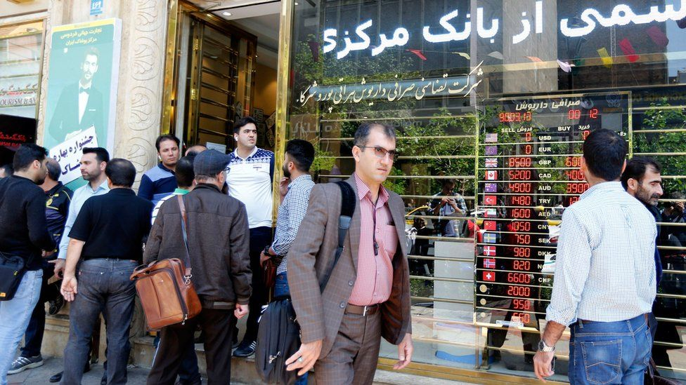 Iranians check foreign currency rates at a shop in Tehran on 10 April 2018