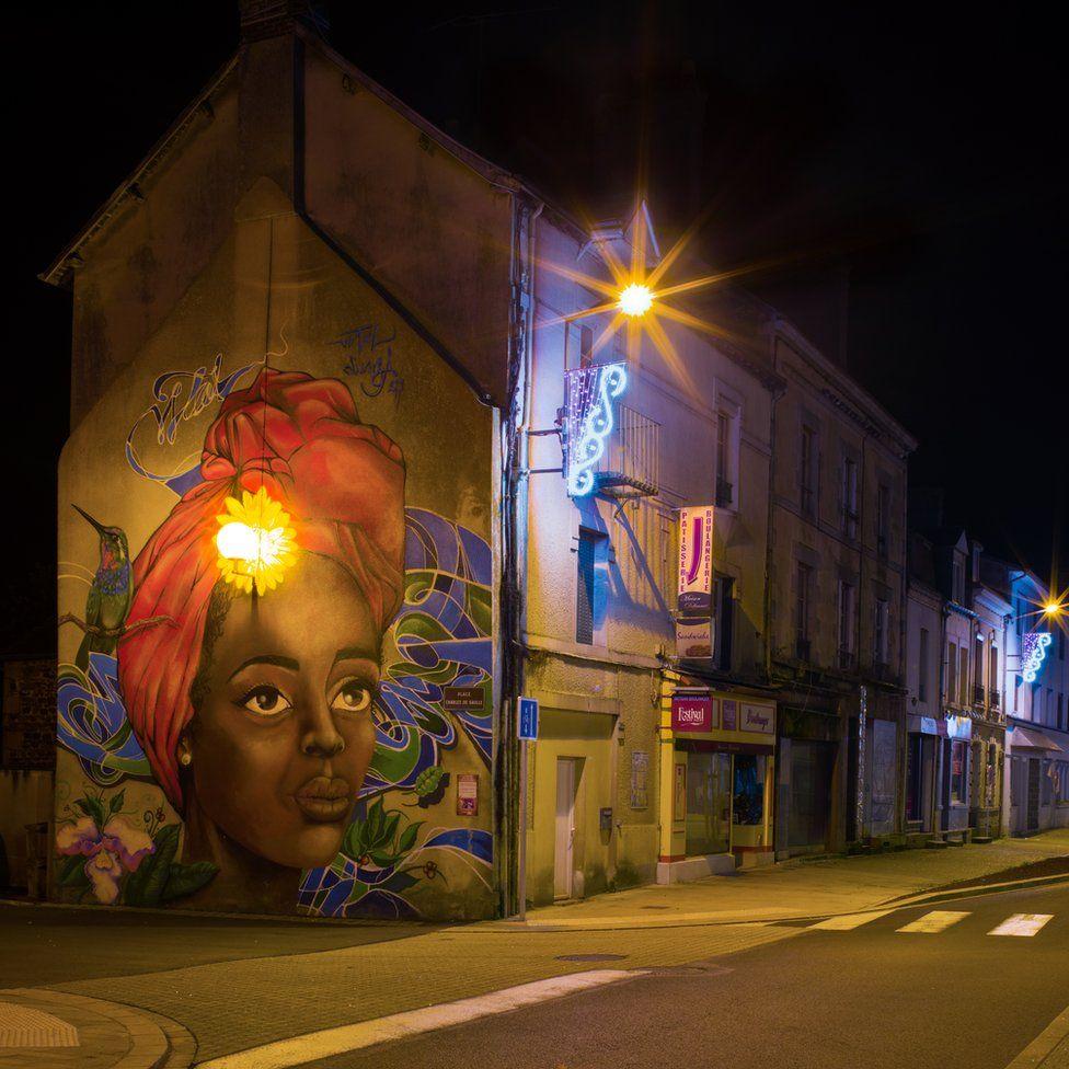 A street light illuminates a mural of a woman's face