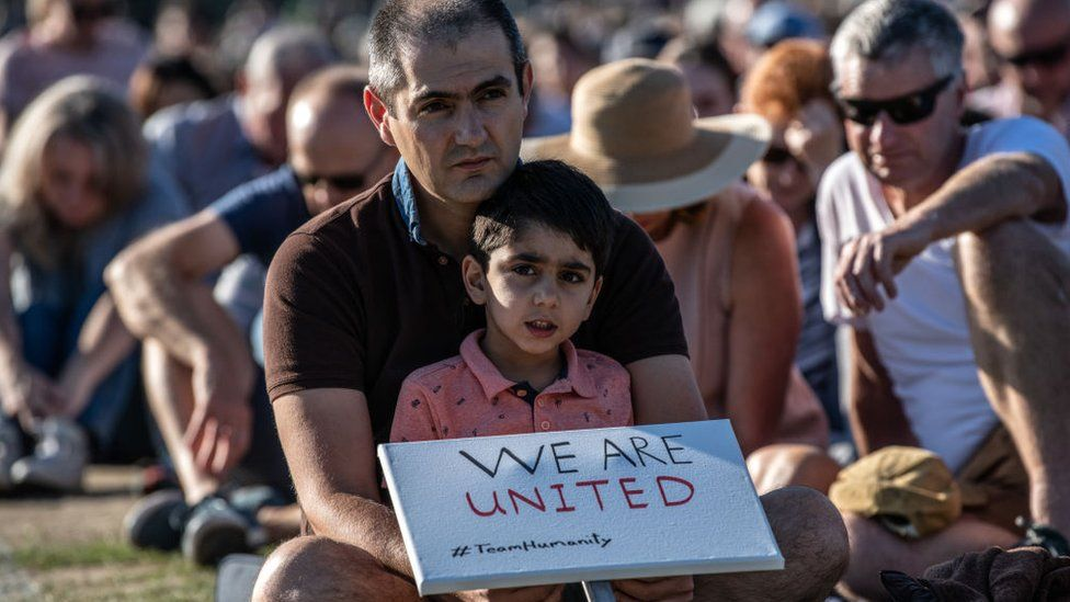 A young boy holds a placard as he takes part in a vigil to remember the victims of the Christchurch mosque attacks, on March 24