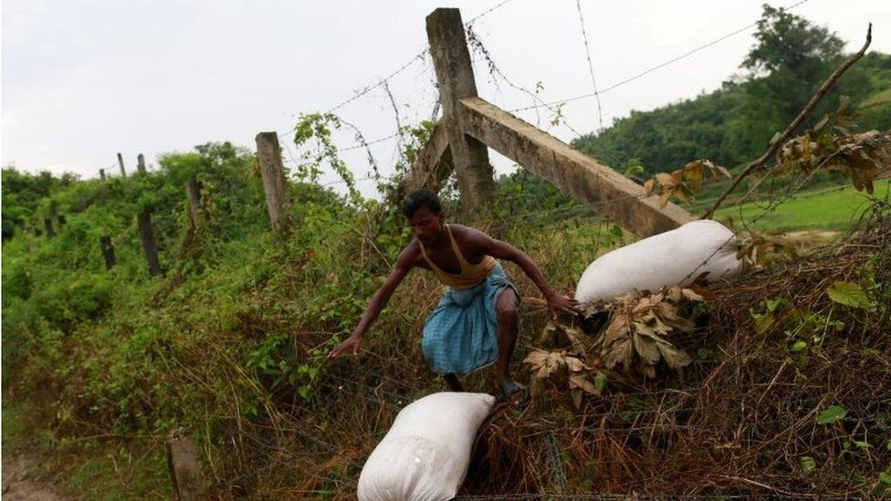 A Rohingya refugee crosses with his belongings over the Bangladesh-Myanmar border fence in Cox's Bazar, Bangladesh,