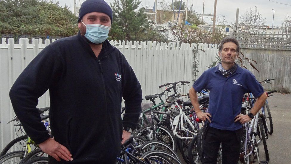 Southern's Dylan Lohman (left) delivers 25 left-behind bikes to Bicycle Technician Paul Horta-Hopkins at SCDA's Newhaven recycling workshop