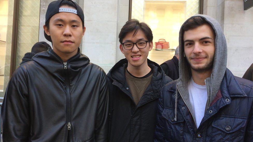 Three men queue for the iPhone X