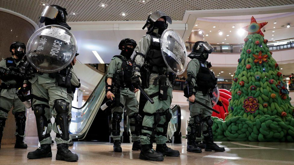 Riot police stand guard next to a Christmas tree inside a shopping mall during an anti-government protest on Christmas Eve at Tsim Sha Tsui in Hong Kong, China, December 24, 2019