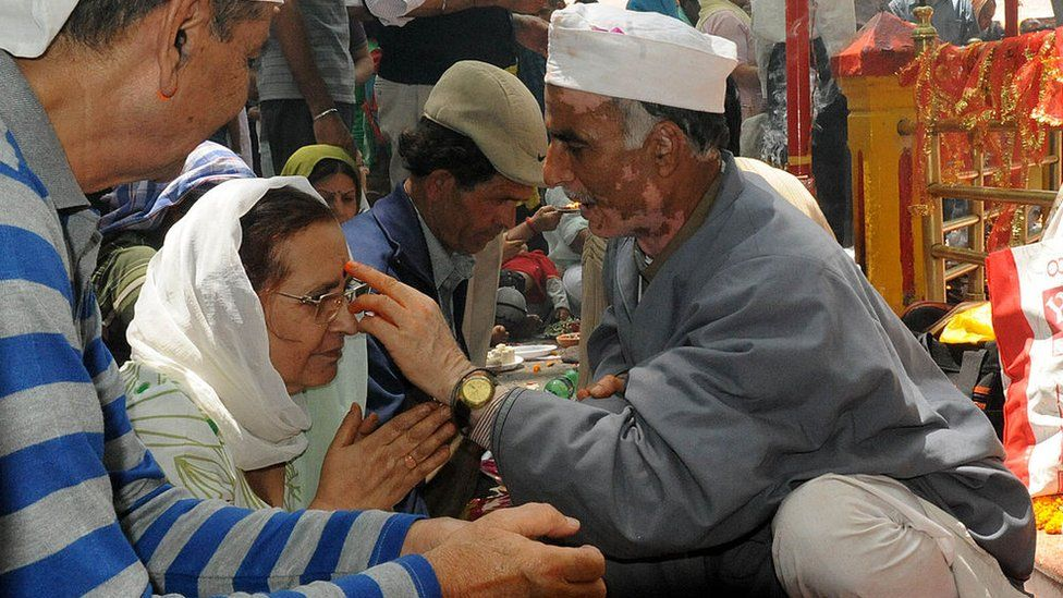 A Hindu priest applies a religious mark on the forehead of an Indian Kashmiri Hindu (Pandit) devotee during the annual Hindu festival at the Khearbhawani temple in Tullamulla village, some 30 kms east of Srinagar on May 29, 2012.