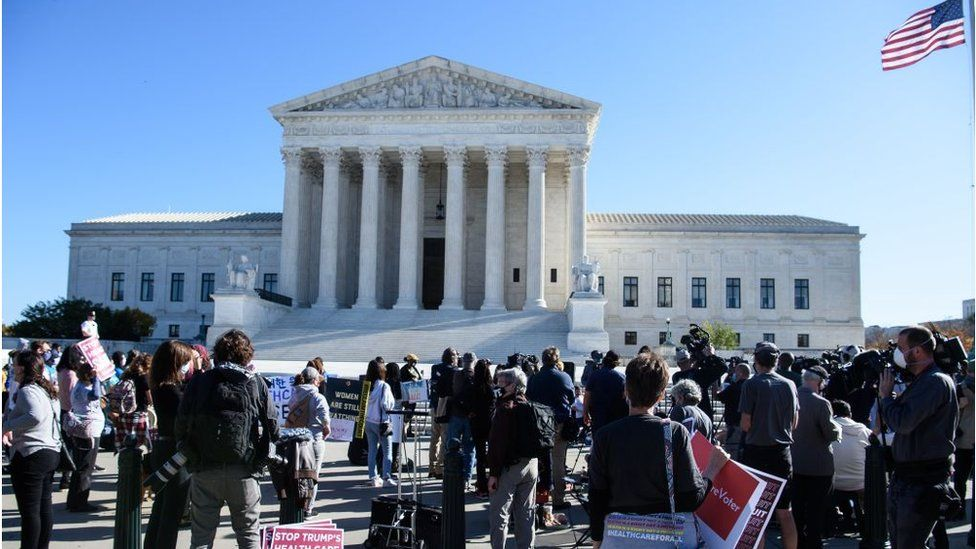 Demonstrators and reporters gather in front of the US Supreme Court in Washington, DC