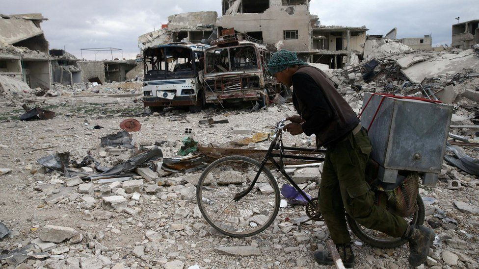 A Syrian man pushes his bike past destroyed buildings in the besieged rebel-held town of Douma on 30 March 2018