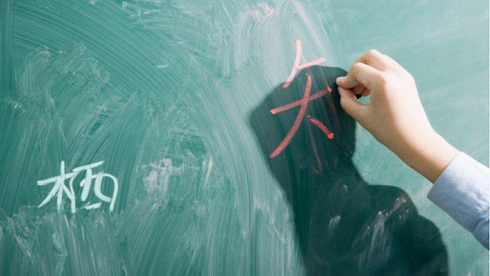 Someone writing Chinese on a blackboard