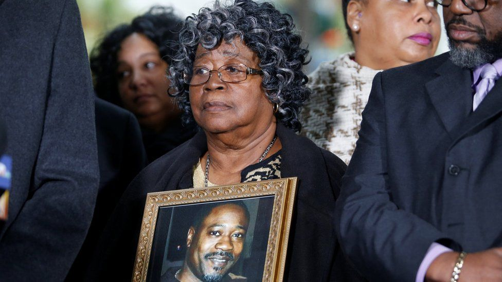 Judy Scott listens while holding a photo of her son Walter Scott during a news conference