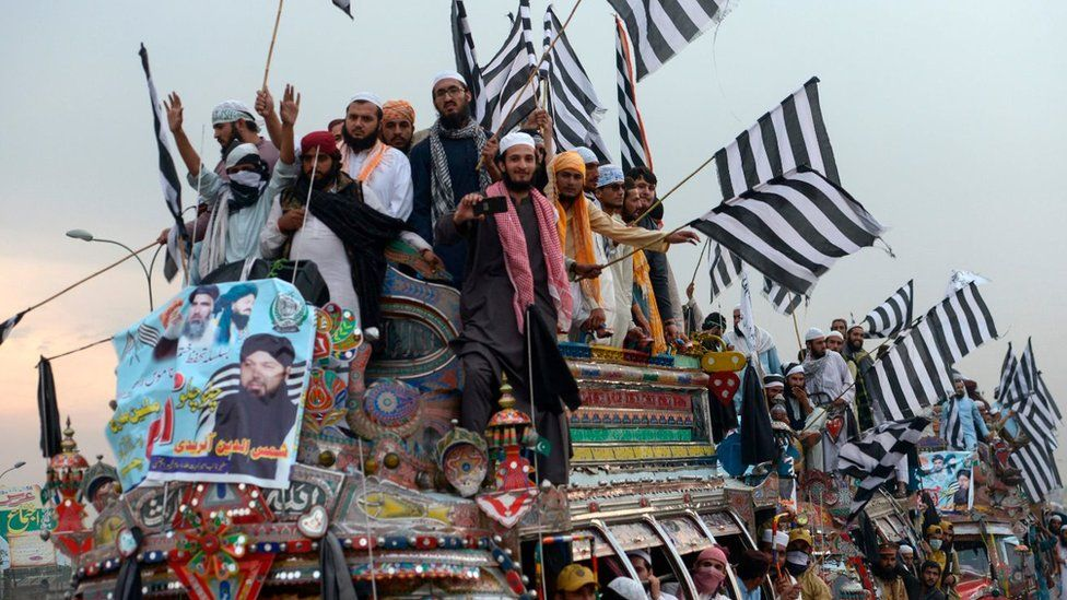 "Supporters of the Islamist Jamiat Ulema-e-Islam (JUI-F) wave party flags atop a vehicle as they take part in an anti-government ""Azadi (Freedom) March"" towards Islamabad, from Peshawar on October 31, 2019"