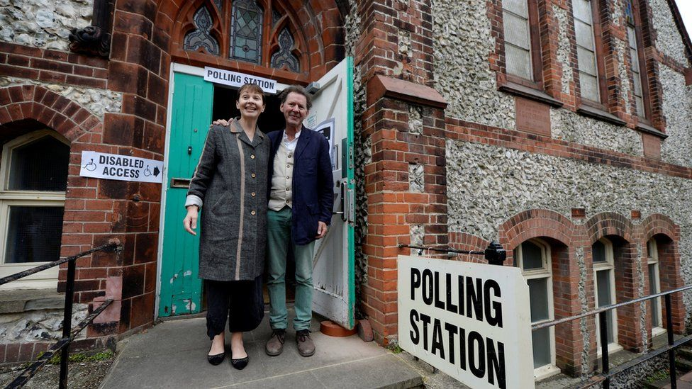 """Caroline Lucas, co-leader of Britain""""s Green Party, arrives with her husband Richard Savage to vote in Brighton"""