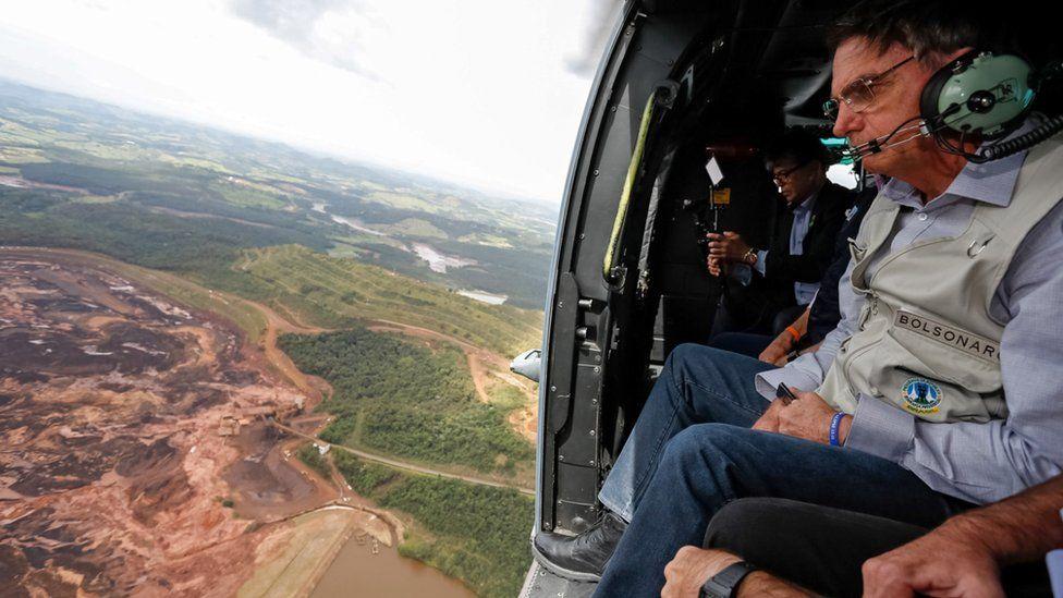 Brazilian President Jair Bolsonaro sits inside a helicopter flying over the area affected by the dam burst near Brumadinho