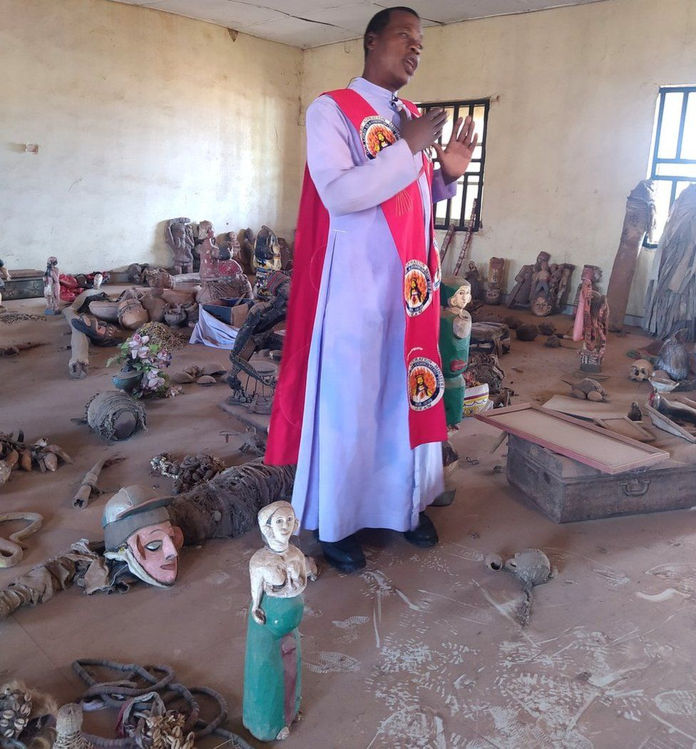 Pastor Obayi standing with artefacts littered on the floors