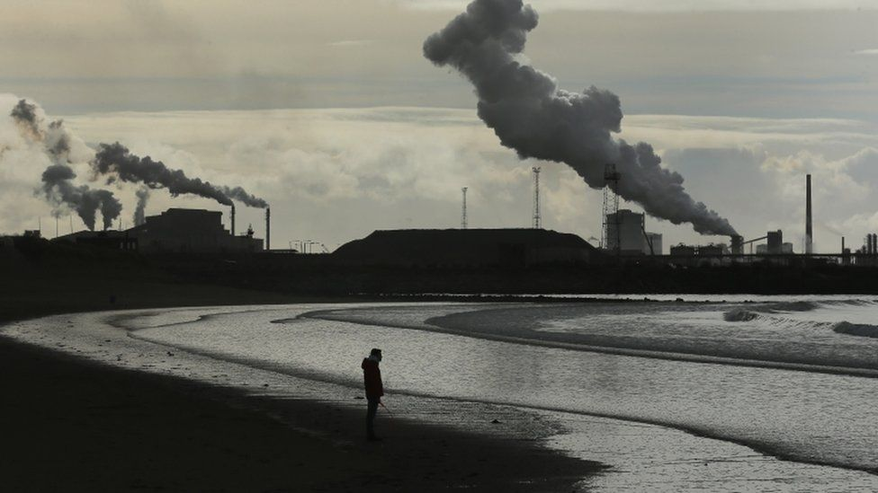 Man on beach by Port Talbot steel plant