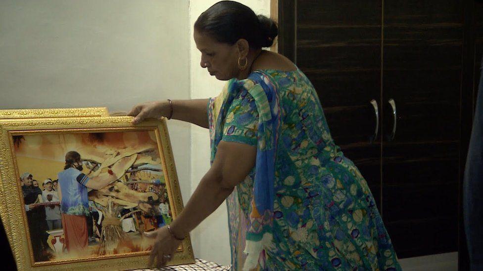 A photo of one Gurmeet Ram Rahim Singh's followers holding a painting of him.
