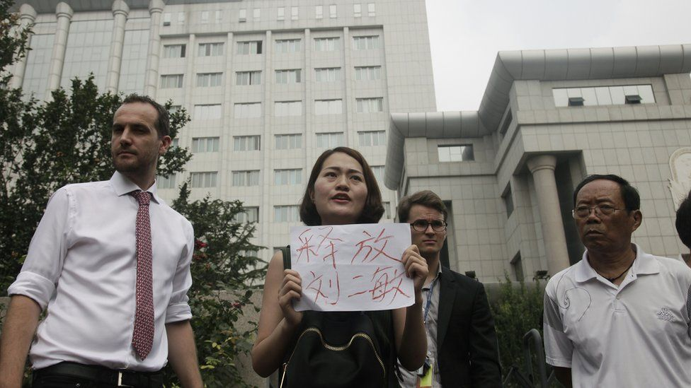 Around two dozen supporters of a prominent Chinese human rights lawyer and three activists charged with subversion protested outside the northern city court amid widespread concerns that authorities were holding their trials in secret