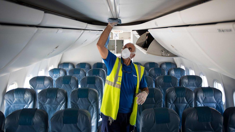 An airline worker wearing a face mask inspects a plane