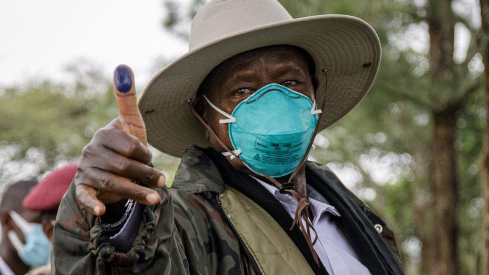 Ugandan President Yoweri Museveni holding up his ink-marked thumb after voting - Thursday 14 January 2021