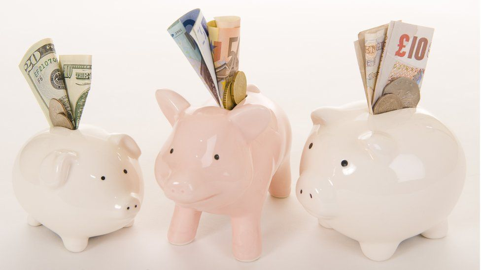 piggy banks with scottish banknotes