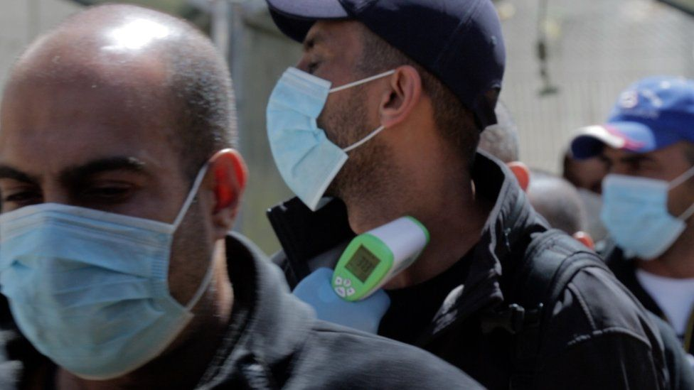 Palestinian medical workers check the temperatures of workers crossing at the Tarqumiya checkpoint, near the West Bank city of Hebron