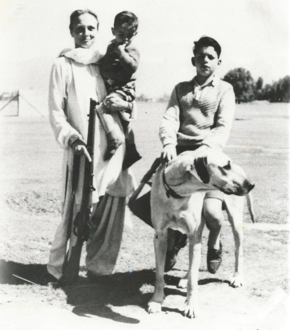 Freda with a rifle when she was living in Kashmir, probably 1948 - she is holding hr son, Kabir, while her older son, Ranga, is sitting on the family's pet dog.