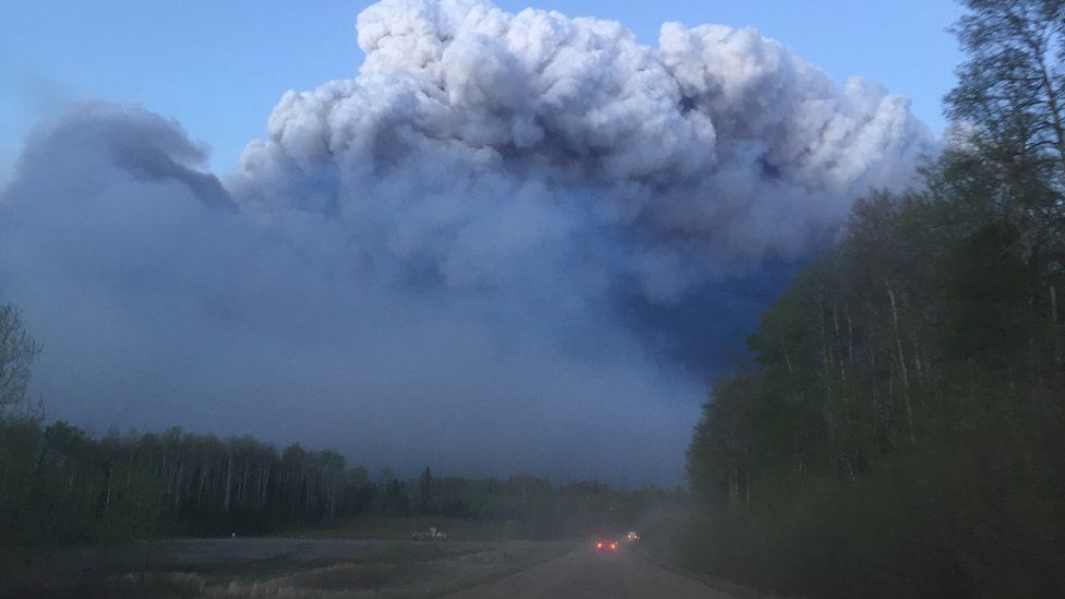 Smoke billows up above a road in Fort McMurray, 5 May 2016
