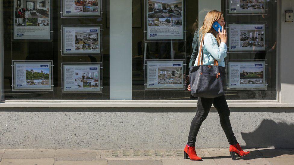 woman walks past estate agents