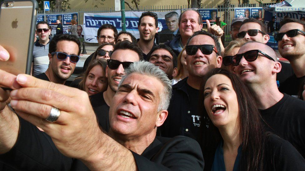 Israeli MP and chairperson of centre-right Yesh Atid party, Yair Lapid, takes a selfie with his wife Lihi (R) and his supporters, outside a polling station on 17 March 2015 in Tel Aviv