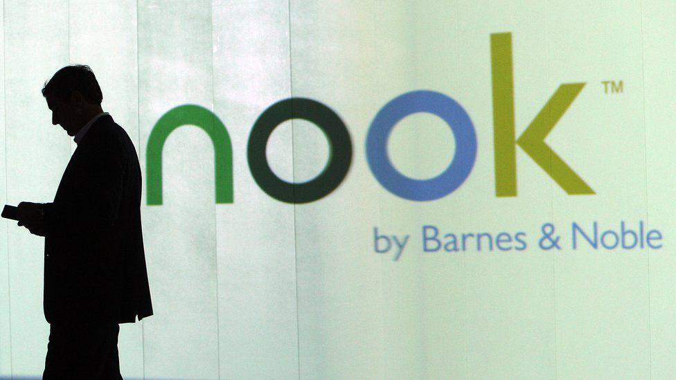 man standing outside Nook advert