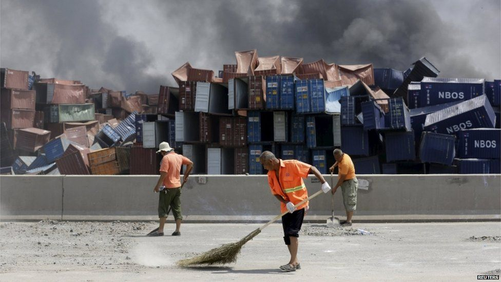 Workers clean a road near the site of the explosions at the Binhai new district, Tianjin, 13 August 2015