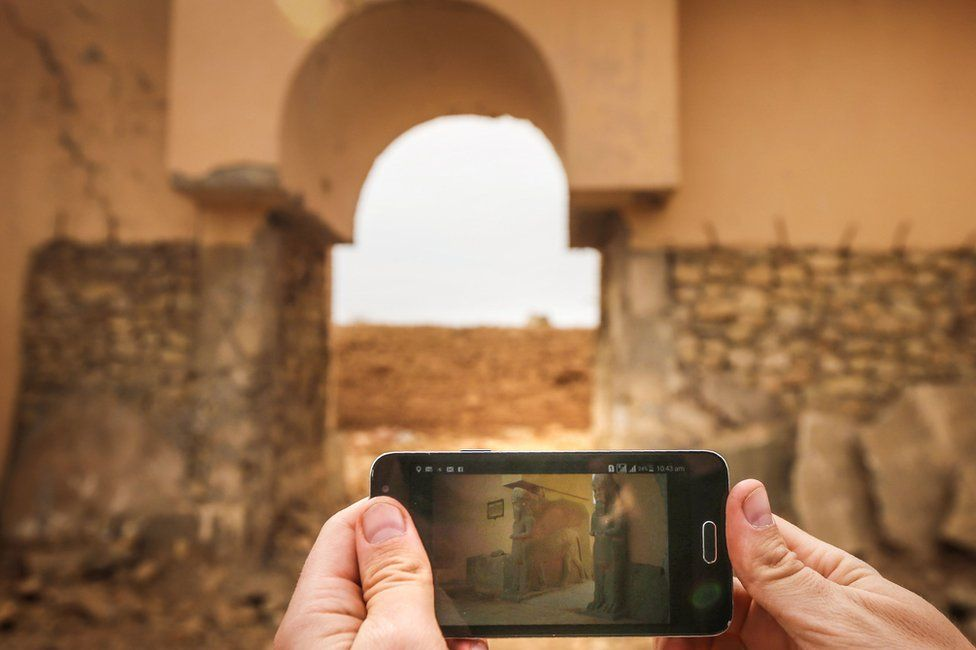A picture taken on 15 November 2016 shows a phone with a picture of the ancient ruins of Nimrud before and after their destruction by IS militants