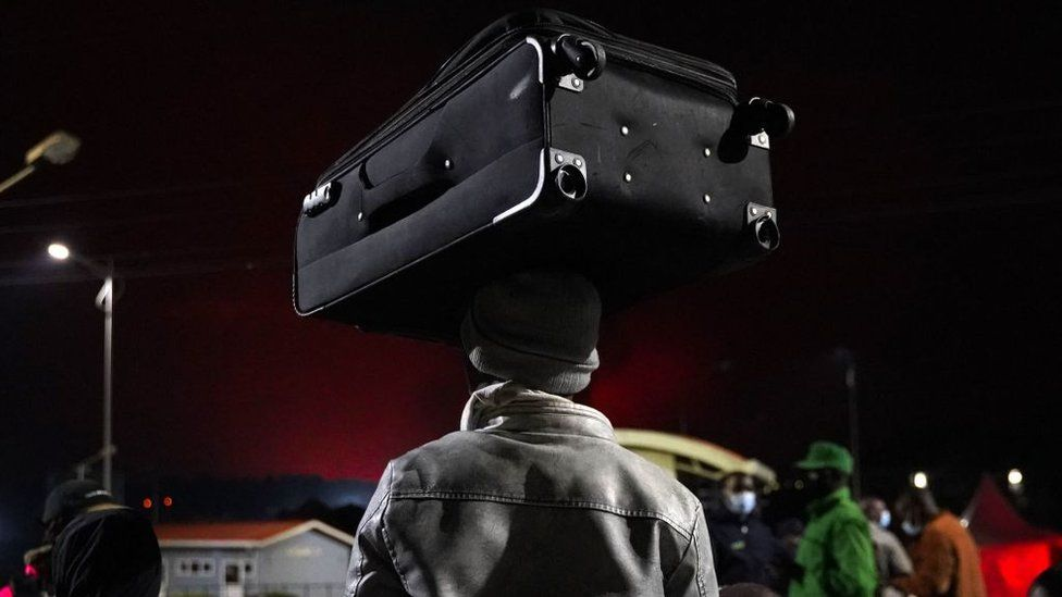 A person carries a suitcase on their head as Congolese people flee from Goma, DRC, after the Nyiragongo volcano erupted, on May 23, 2021