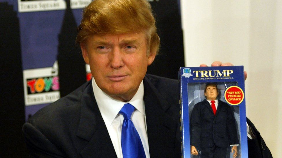Donald Trump holds up a Trump doll at a Toys 'r' Us event in 2004.