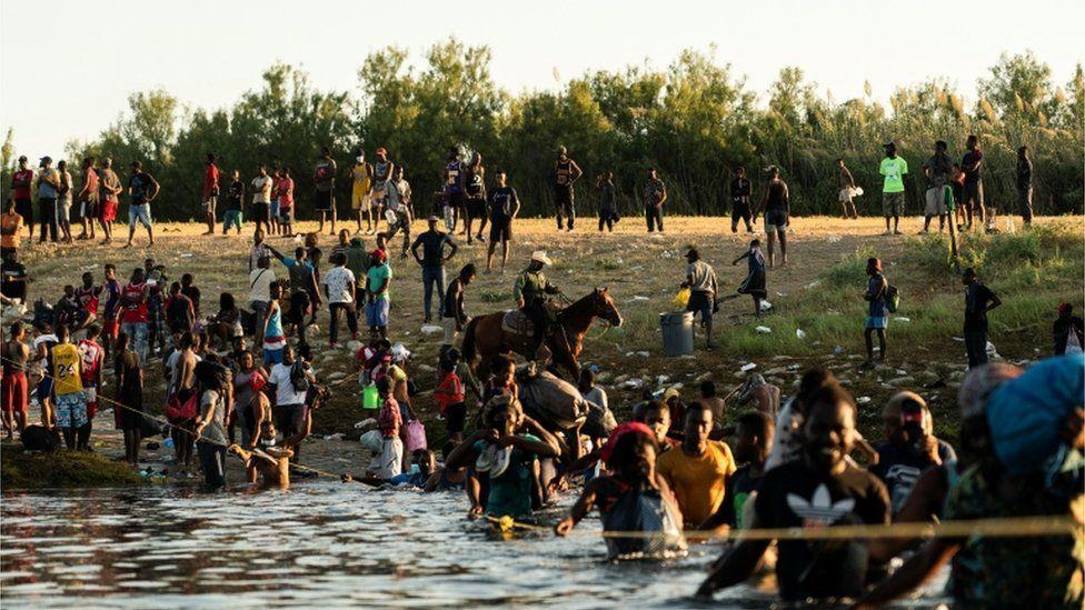 Border Patrol agents on horseback push Haitians back from the US border
